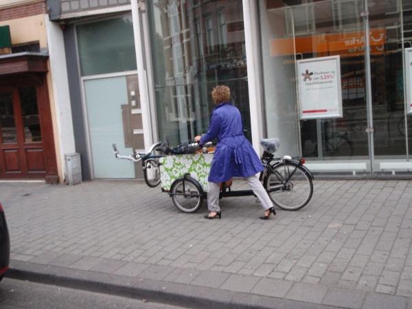 Vrouw met twee fietsen, een gewone fiets in een bakfiets