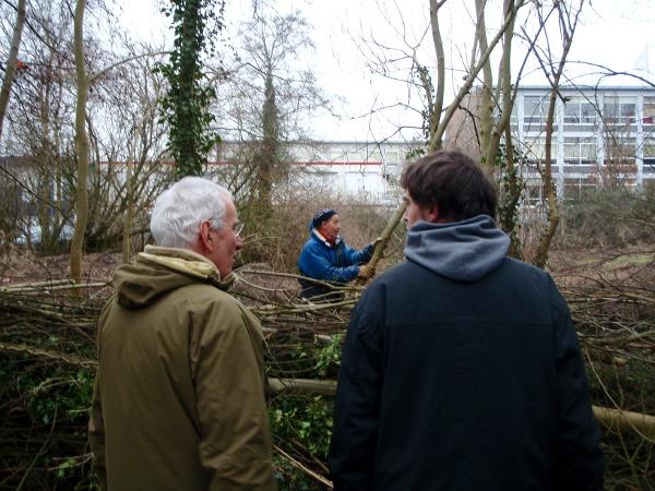 Marc en Sjef praten terwijl aan de waterkant bomen worden omgezaagd