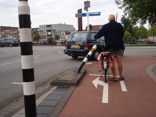 Een paaltje met een knopje voor het stoplicht staat scheef op de kruising Lange Herenvest - Schalkwijkerstraat