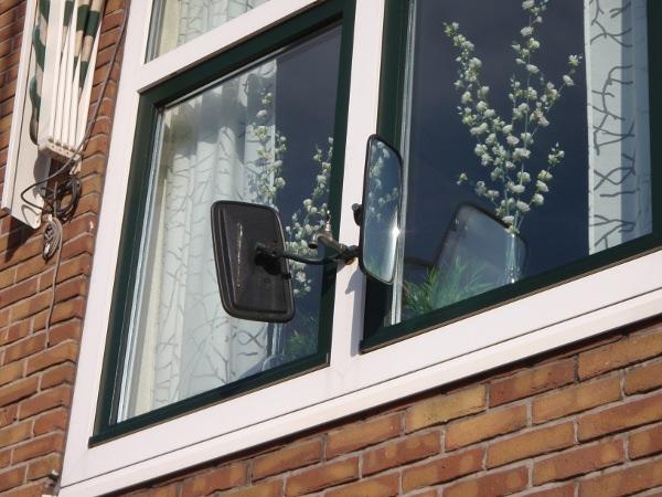 Spiegels op een raam van een huis om de straat in te kijken